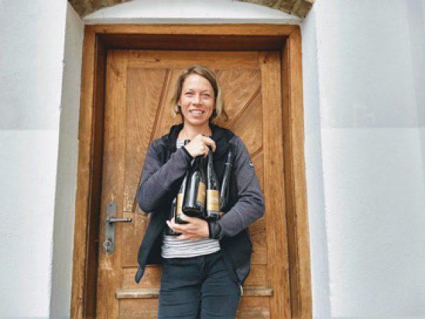 Silke Mayr vor einer Tür mit vielen Flaschen im Arm
